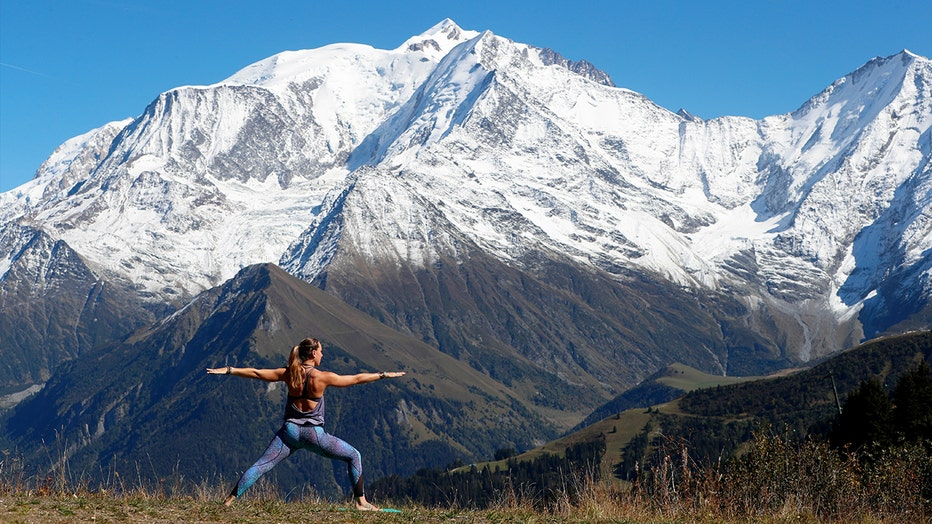 French Alps. Mont-Blanc massif. Woman doing yoya meditation on mountain. Saint-Gervais, France.
