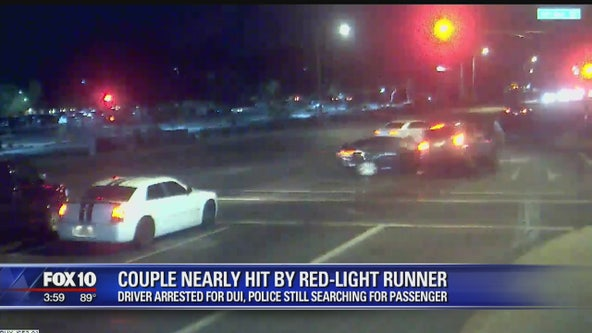 Car crashes into suspected drunk driver running red light, possibly saving couple's lives