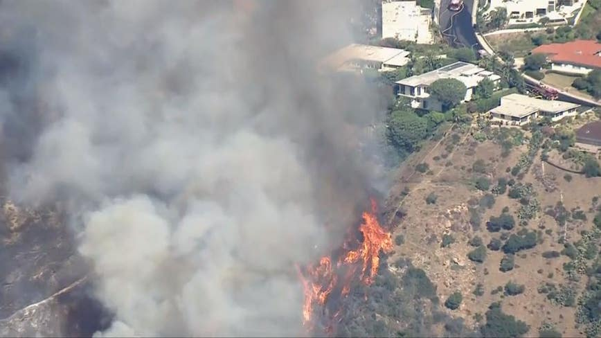 Fire crews battle rapidly growing uphill brush fire in Pacific Palisades
