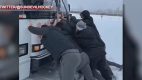 ASU hockey team pushes stuck bus out of snow in Alaska