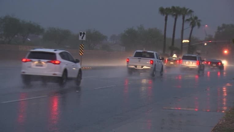 Screenshot taken from video of rain along a stretch of road in Surprise, Arizona. Cars are driving on the wet road