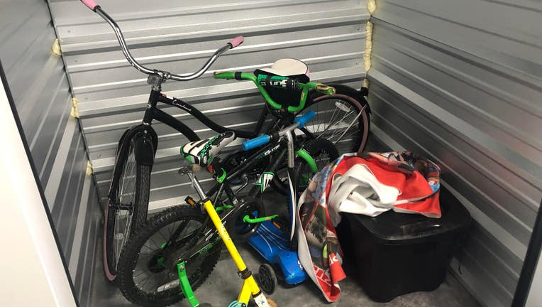 Storage unit with two bikes, a scooter, a bin, a couple of blankets