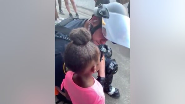 Police officer comforts crying little girl who asked 'are you gonna shoot us?' during protest