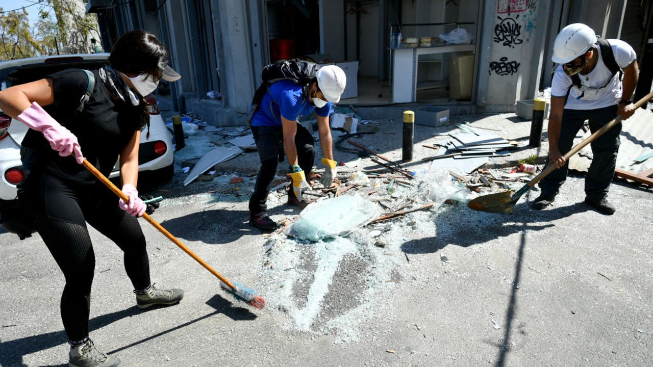 Lebanese clear blast rubble from roads around cratered...