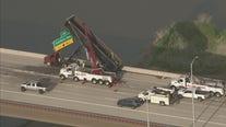 Dump truck crashes into freeway sign