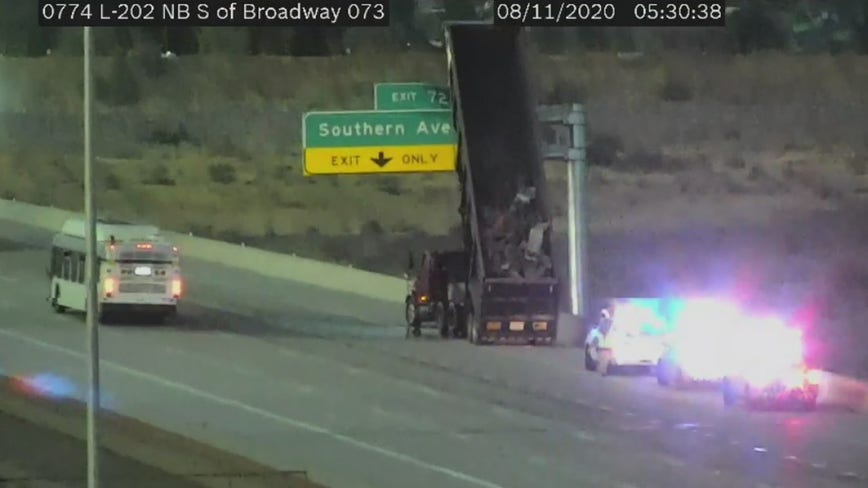 Dump truck with upright bed hits freeway sign