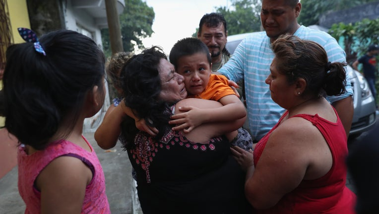 Child being embraced by family members