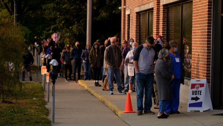 Several voters wearing masks are seen lined up outside