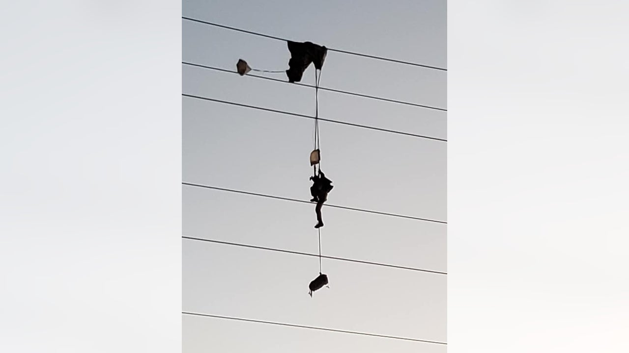 Paratrooper entangled in high-voltage power lines, requiring rescue