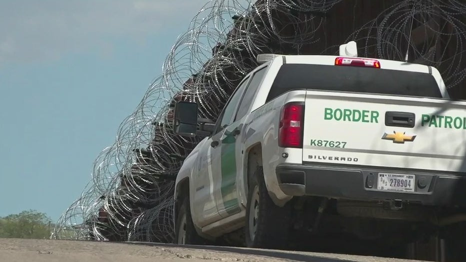 A Border Patrol truck next to the U.S. - Mexico border wall.
