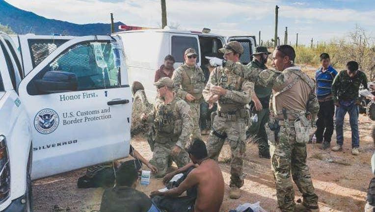 Border patrol agents gathered around migrants