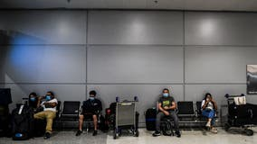 US to keep international travel restrictions for now, citing virus surge