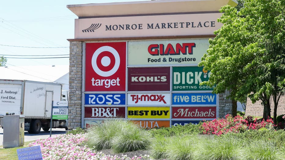 A sign at the entrance of Monroe Marketplace shows the logos