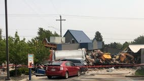 Driver charged after dump truck plows into cars, buildings