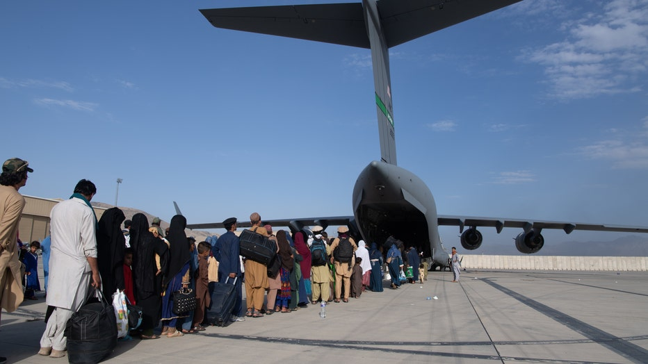 People board a U.S. Air Force C-17 Globemaster III at Hamid Karzai International Airport in Kabul, Afghanistan.