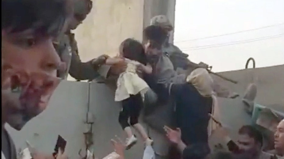 Storyful-258883-Young_Child_Hoisted_Over_Wall_Amid_Chaos_at_Kabul_Airport.mp4.00_01_19_14.Still001