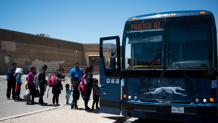 Buses idle in the noon sun waiting to take migrant families to reunite with their families in Yuma