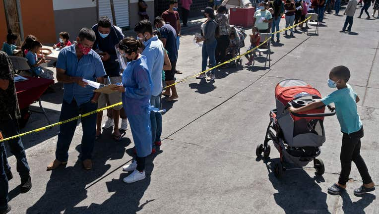 Asylum seekers camping at El Chaparral crossing port queue to be vaccinated against COVID-19