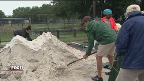 Local officials hand out sandbags to combat area flooding