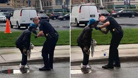 Bystanders watch officer help man shave on Detroit street
