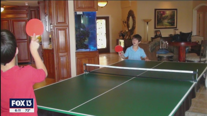 Brothers practice ping pong hundreds of miles apart thanks to robotic pitching machine