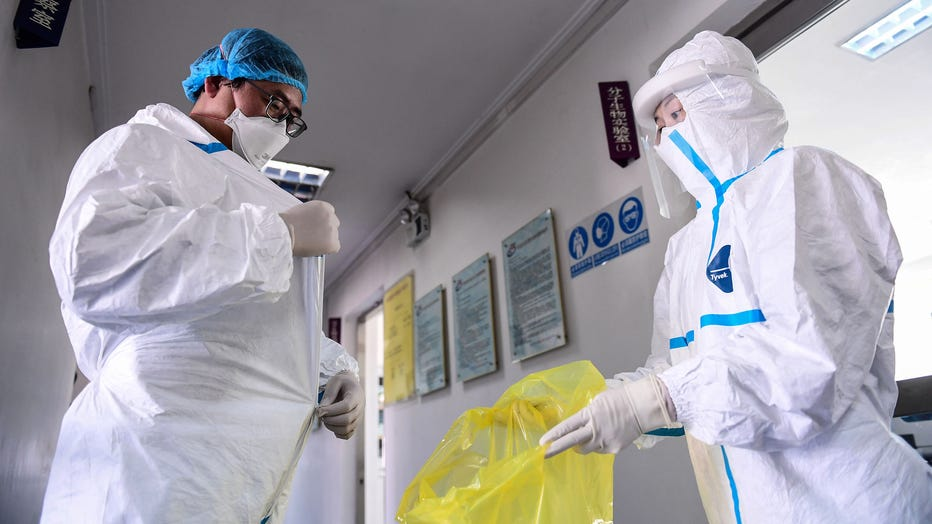 A laboratory technician removes his protective suit after leaving a laboratory in Shenyang in China's northeastern Liaoning province on Feb. 12, 2020. (Photo by STR/AFP via Getty Images)