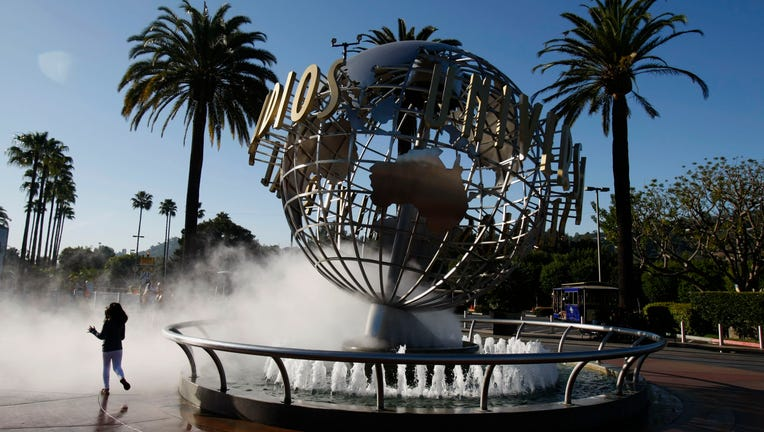On a beautiful day in Southern California, Pammy Hamm, 6, runs through the spray at the entrance of