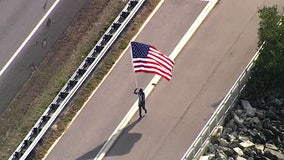 With U.S. flag in hand, 'Running Man' honors all essential workers along Courtney Campbell