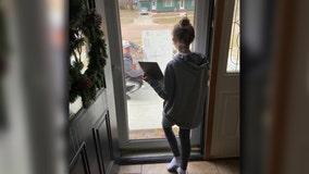 Math teacher brings over whiteboard to help student through glass door