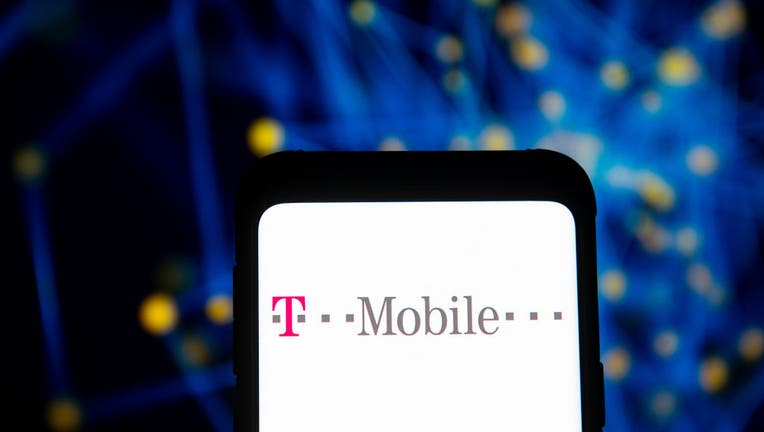 In this photo illustration a T-Mobile logo seen displayed on