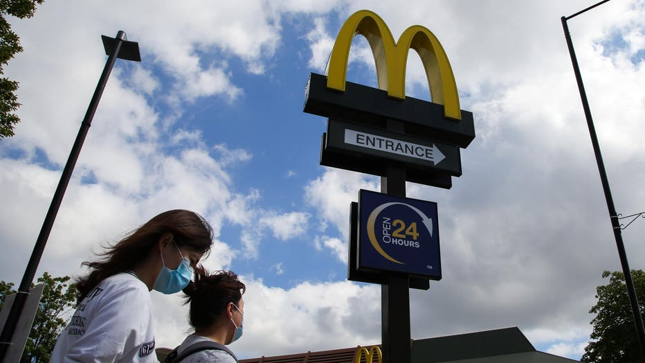 Women wearing face masks walks past a McDonald's logo