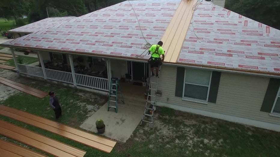 Man putting up new roof for foster family