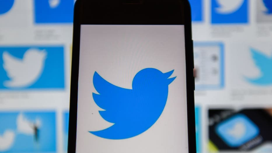 In this photo illustration a Twitter logo seen displayed on