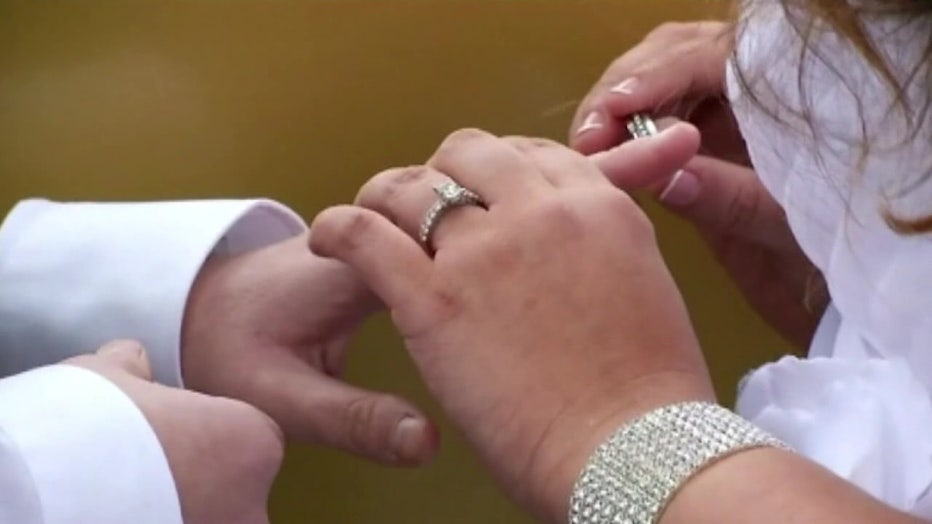 couple putting on rings at wedding