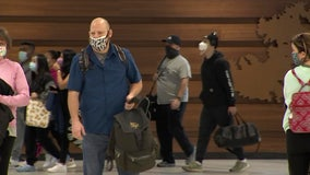With masked faces and cautious optimism, holiday travelers arrive at the airport