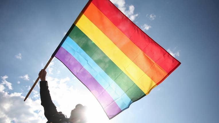 A Polish wave a rainbow flag as he takes