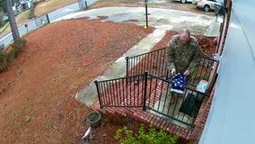 Man in fatigues filmed folding torn US flag