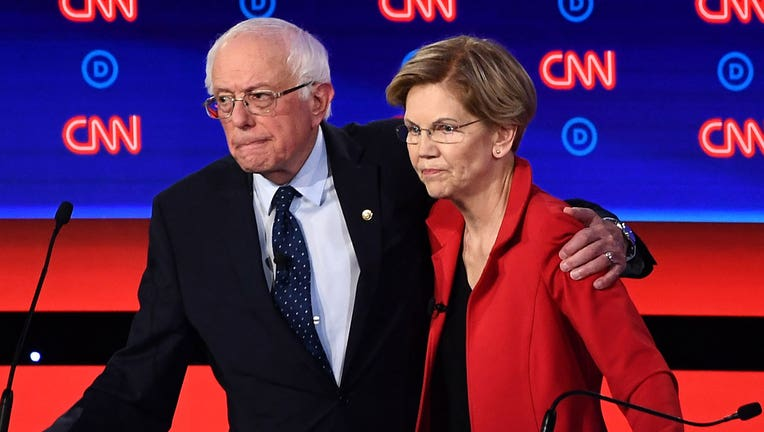 Sens. Bernie Sanders and Elizabeth Warren are shown in a file photo from a Democratic debate. (Photo by Brendan Smialowski / AFP)