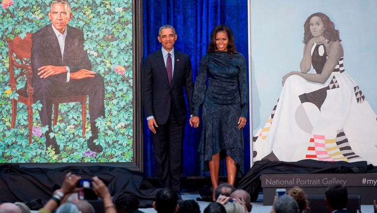 TOPSHOT - Former US President Barack Obama and First Lady Michelle Obama stand beside their portraits after their unveiling at the Smithsonian's National Portrait Gallery in Washington, DC, February 12, 2018. (Photo by SAUL LOEB / AFP) / RESTRICTED TO EDITORIAL USE - MANDATORY MENTION OF THE ARTIST UPON PUBLICATION - TO ILLUSTRATE THE EVENT AS SPECIFIED IN THE CAPTION (Photo credit should read SAUL LOEB/AFP via Getty Images)