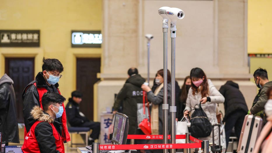 Staff members screen arriving passengers with thermal scanners at Hankou railway station in Wuhan, in China's central Hubei province on January 21, 2020. - Asian countries on January 21 ramped up measures to block the spread of a new virus as the death toll in China rose to six and the number of cases surpassed 300, raising concerns in the middle of a major holiday travel rush.