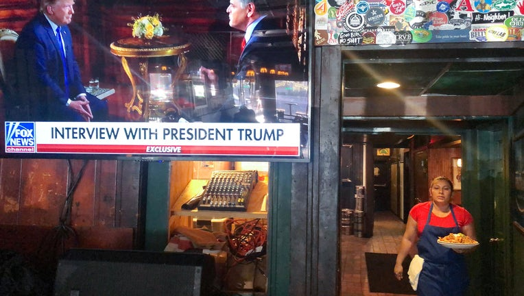 FILE - President Donald Trump's pre-game Super Bowl interview with Fox News host Sean Hannity is broadcast in a bar on February 2, 2020 in Washington, DC.