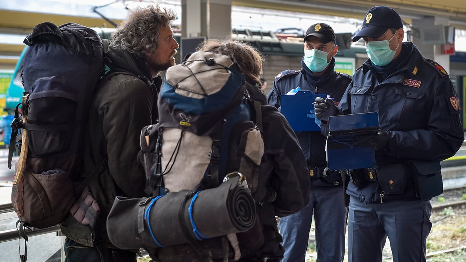 Police officers check passengers leaving from Turin Porta