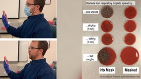 Doctor demonstrates how face mask blocks respiratory droplets from spreading