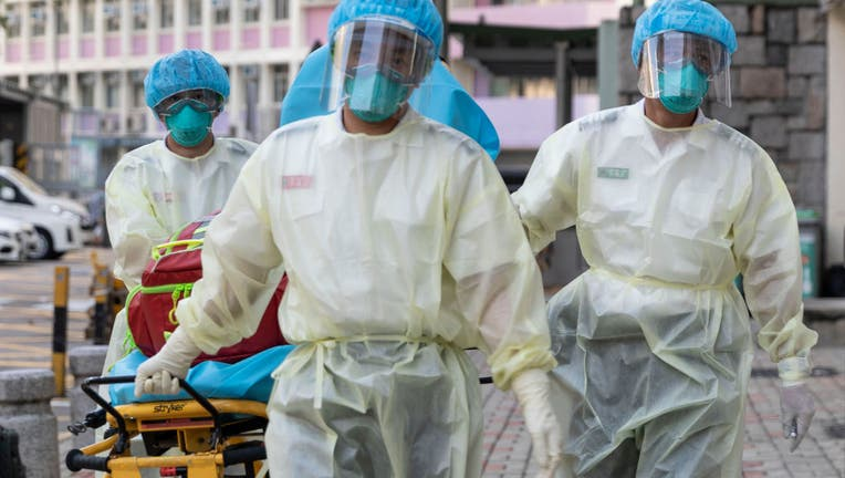 FILE - Medical staff wearing personal protective equipment (PPE) as a precautionary measure against the COVID-19 coronavirus approach Lei Muk Shue care home in Hong Kong on August 23, 2020.