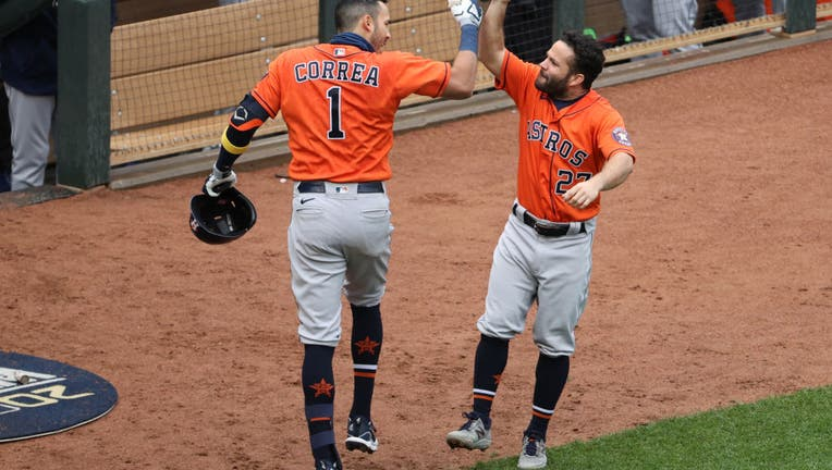 Carlos Correa #1 and Jose Altuve #27 of the Houston Astros celebrate after Correa hit a home run in the seventh inning of Game 2 of the Wild Card Series between the Houston Astros and the Minnesota Twins at Target Field on Wednesday, September 30, 2020 in Minneapolis, Minnesota.