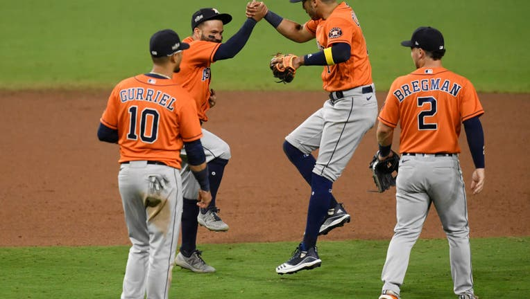 Jose Altuve #27 and Carlos Correa #1 of the Houston Astros celebrate a 7-4 win against the Tampa Bay Rays in Game Six of the American League Championship Series at PETCO Park on October 16, 2020 in San Diego, California.