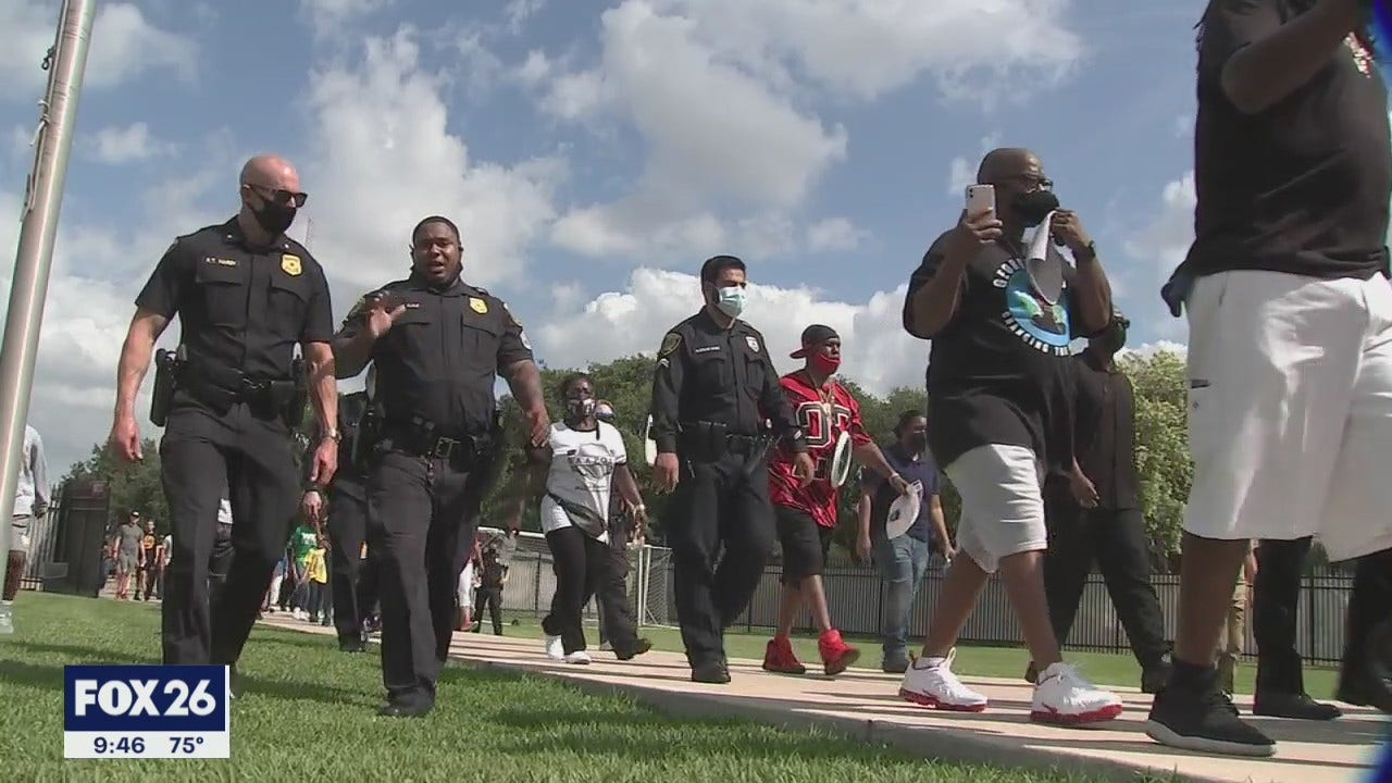 Houston police officers march side-by-side with protestors