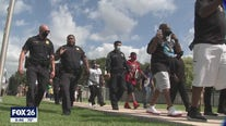 Officers march side-by-side with protesters for Stop the Violence Rally
