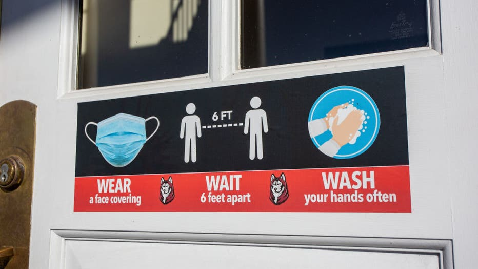 A sign that reminds people to wear a mask, wash their hands