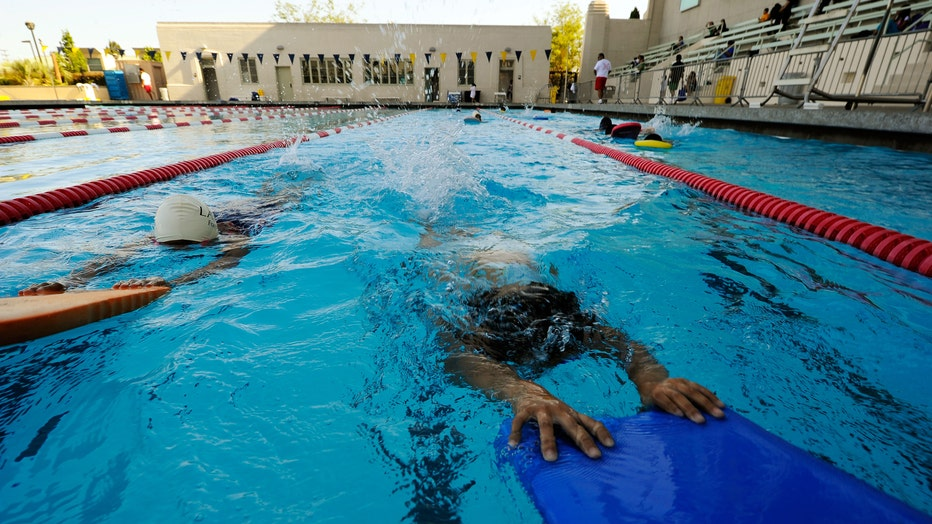 Adults and kids swim in Los Angeles outdoor pool.